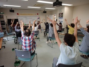 介護予防教室の風景です。両手を大きく上げて体を伸ばします。
